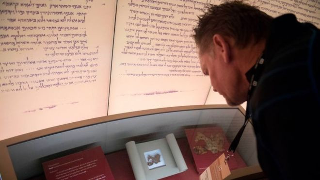 A visitor at the Bible Museum's Dead Sea Scrolls exhibit - where all the fragments have been found to be fake. (Getty Images)