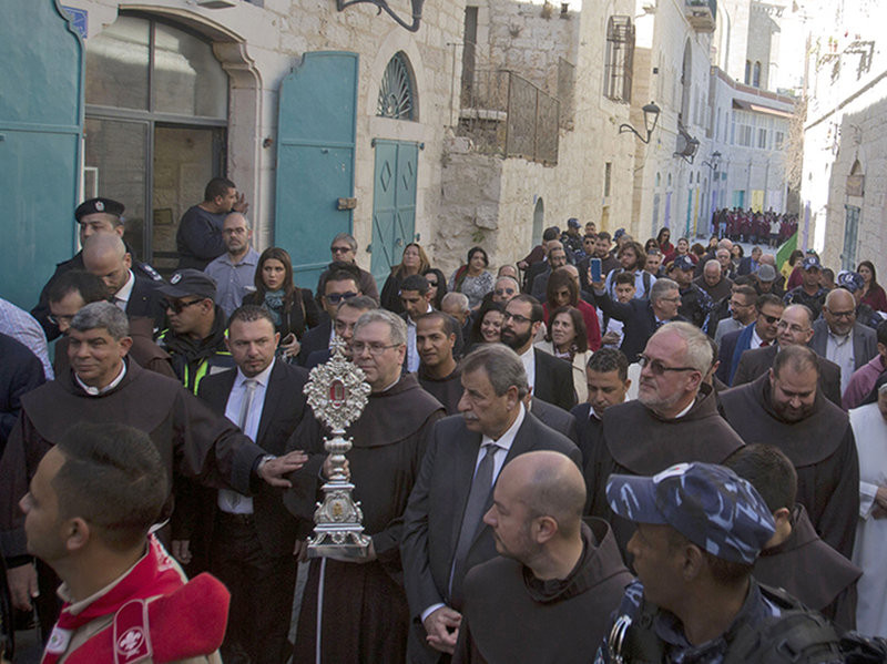Clergymen carry a wooden relic believed to be from Jesus' manger outside the Church of the Nativity, in Bethlehem, on Saturday. (Majdi Mohammed/AP)