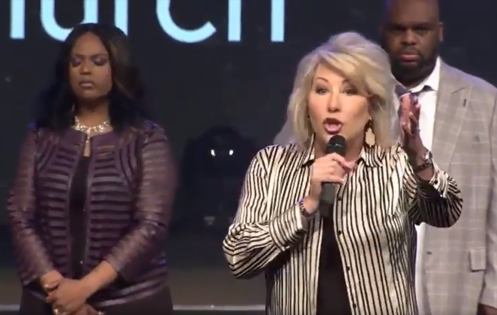 Hope Carpenter speaks before the congregation at Relentless Church while Pastors John and Aventer Gray stand behind her.