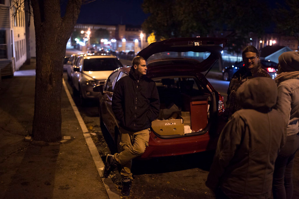Jesse Harvey, left, stands by the open trunk of his car offering naloxone, clean needles, and other supplies to people in Lewiston, ME. (Photo by: Brianna Soukup/Portland Press Herald)