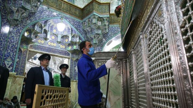 Iranian sanitary workers disinfect Qom's Masumeh shrine. (Getty Images)