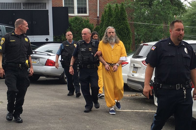 Lee Kaplan (yellow jumpsuit) being led to a preliminary hearing in August of 2016