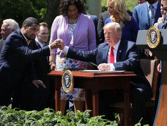 President Trump shakes hands with a pastor during the signing ceremony on Thursday.