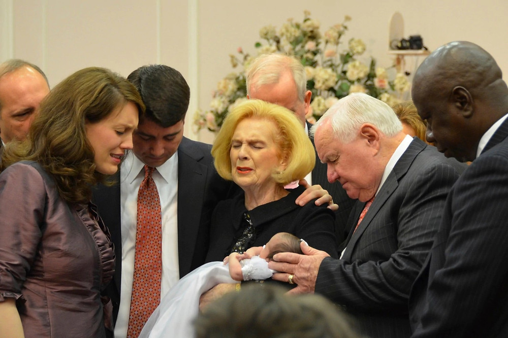 Jane Whaley, center, holds a baby during a church service.