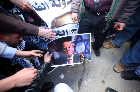 Palestinian protesters set fire to a photo of President Trump