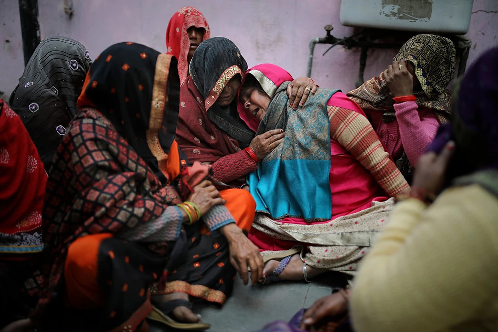 Mourning a victim of the clashes outside a mortuary in New Delhi on Wednesday. (Altaf Qadri/Associated Press)