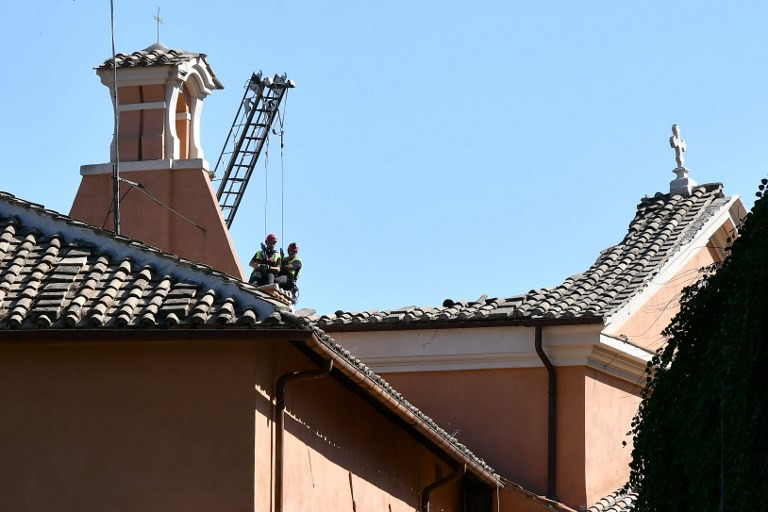 Firefighters attempt to stabilize the remaining portion of the roof of the church. Photo: Alberto Pizzoli/AFP