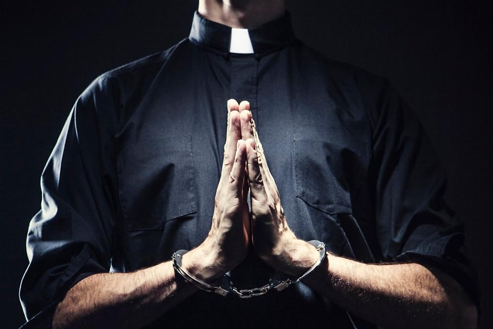 Priest in handcuffs...