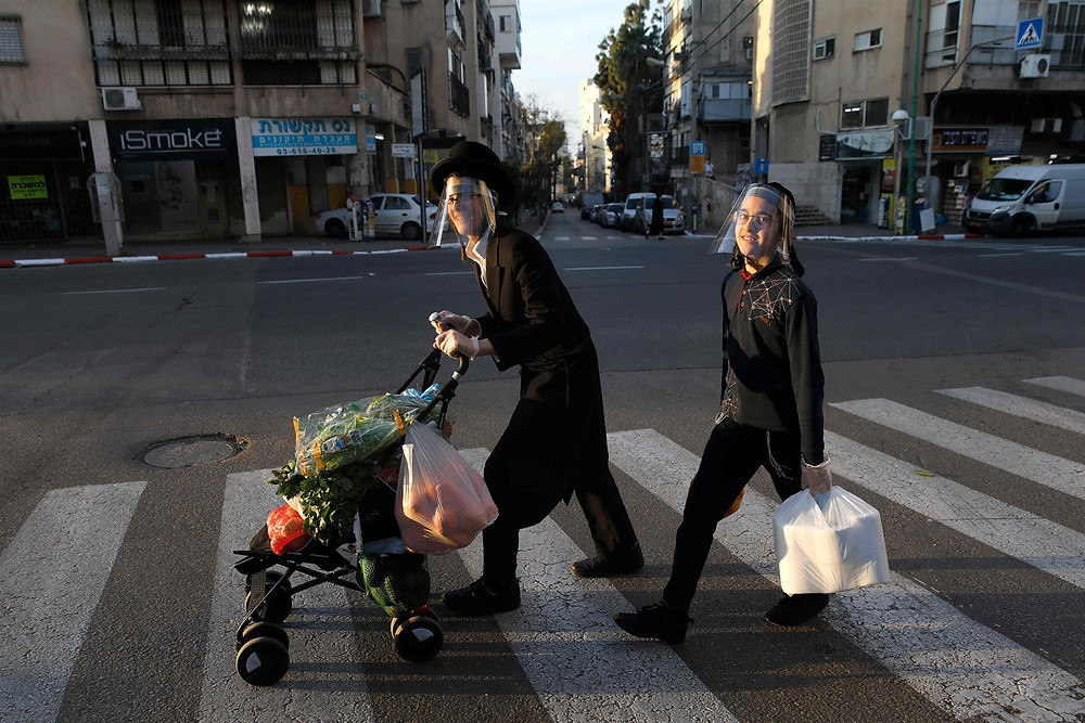 Ultra-Orthodox Jewish youths wearing protective plastic masks cross a street with their shopping at the city of Bnei Brak near Tel Aviv on Thursday. (Menahem Kahana/AFP-Getty Images)