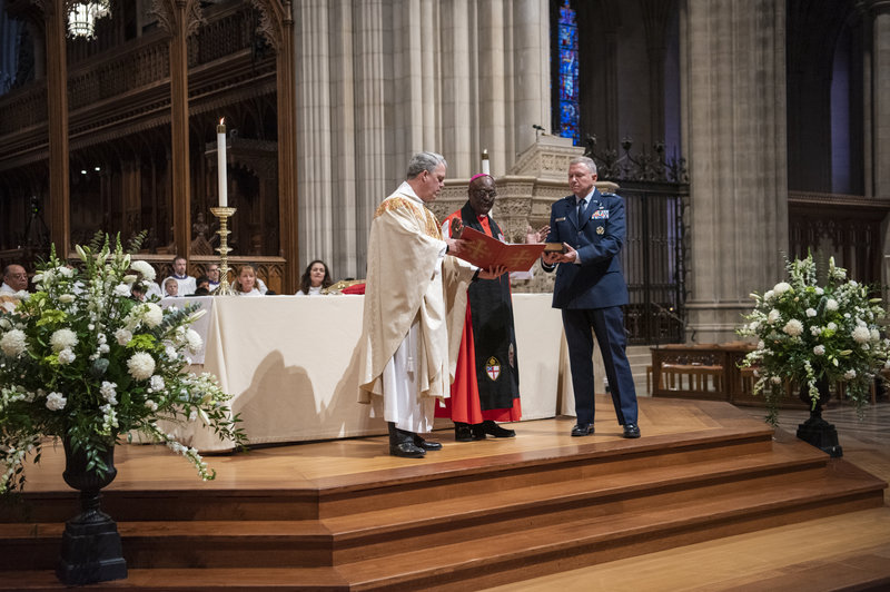 The Rev. Randolph Hollerith (left), the Rev. Carl Wright, and Maj. Gen. Steven Schaick, the Air Force chief of chaplains, participate in the blessing of a Bible for swearing in U.S. Space Force officials. [Danielle E. Thomas/Washington National Cathedral]