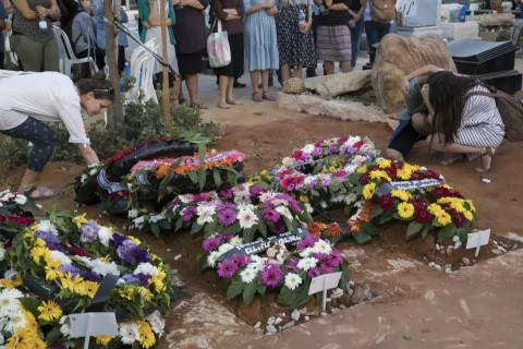 Mourners gather near the graves of the Salomon family.