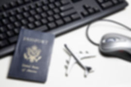Computer mouse, toy airplane, passport and keyboard placed on a white tabletop.jpg