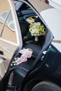 Groom in the car, holding wedding bouquet before ceremony