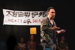 "Daniel performs in front of a banner that says ""Liberty or Death""."