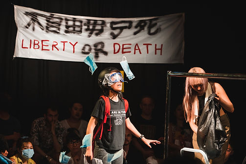 """Bonnie Chan performs with an eye shield and a red backpack on. The banner hanged behind says. """"Liberty or death""""."""