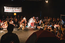 Audience sitting at the peripheral in a black box theatre while Yik Sau performs in the middle