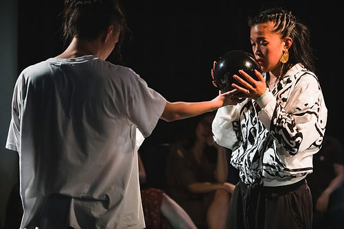 Julia Tang receives a bowl from a dancer.