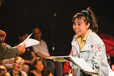 Siu-See Hung holds a scripts as she engages in a dialogue with another actor out of frame.