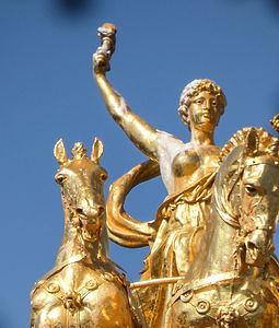 gold-colored statue of woman riding on carriage_edited_edited.jpg