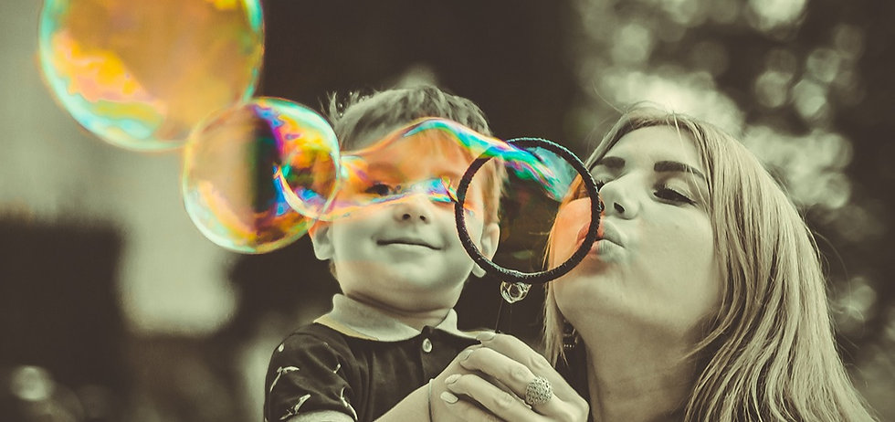 Young mom and child blowing bubbles - focusing on life.