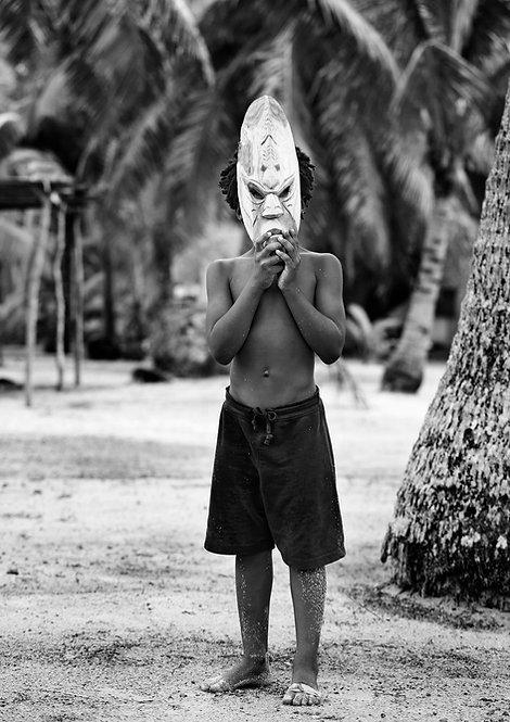 boy showing fijian wood mask