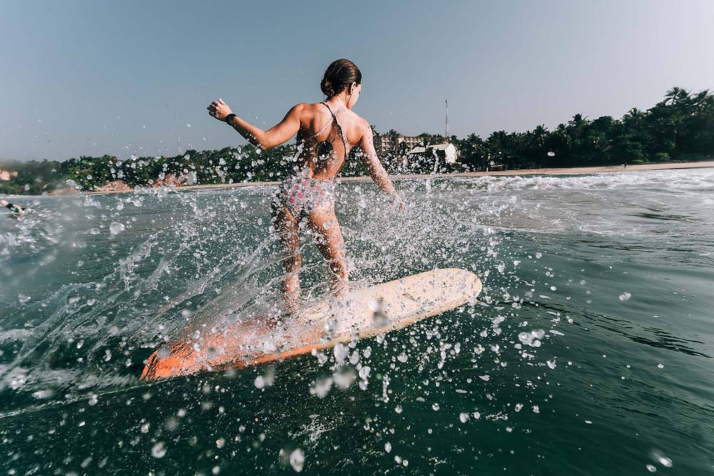 Kate auf dem Longboard in tropischen Gewässern