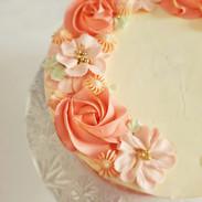 Peach buttercream blossoms on white buttercream