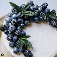 Fresh blueberries and mint top vanilla cake