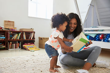 Mother And Baby Daughter Reading Book In