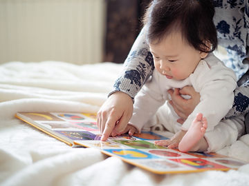 Asian baby girl reading book with mom.jp