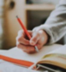 person-holding-orange-pen-1925536-765x49