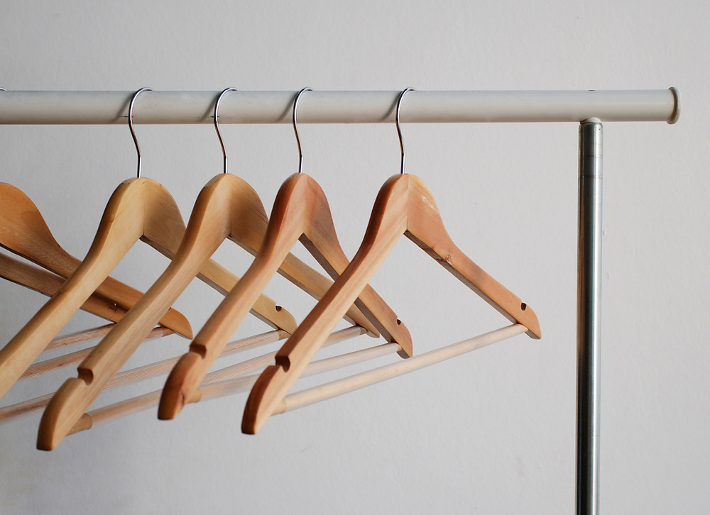 Empty hangers hanging on clothes rack.