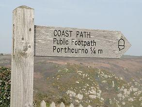 A sign post on the Cornish Coastal Path at Porthcurno