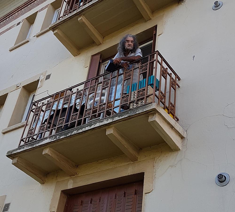 il surveille son jardin du balcon