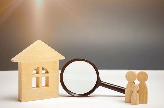 Wooden house and magnifying glass with f