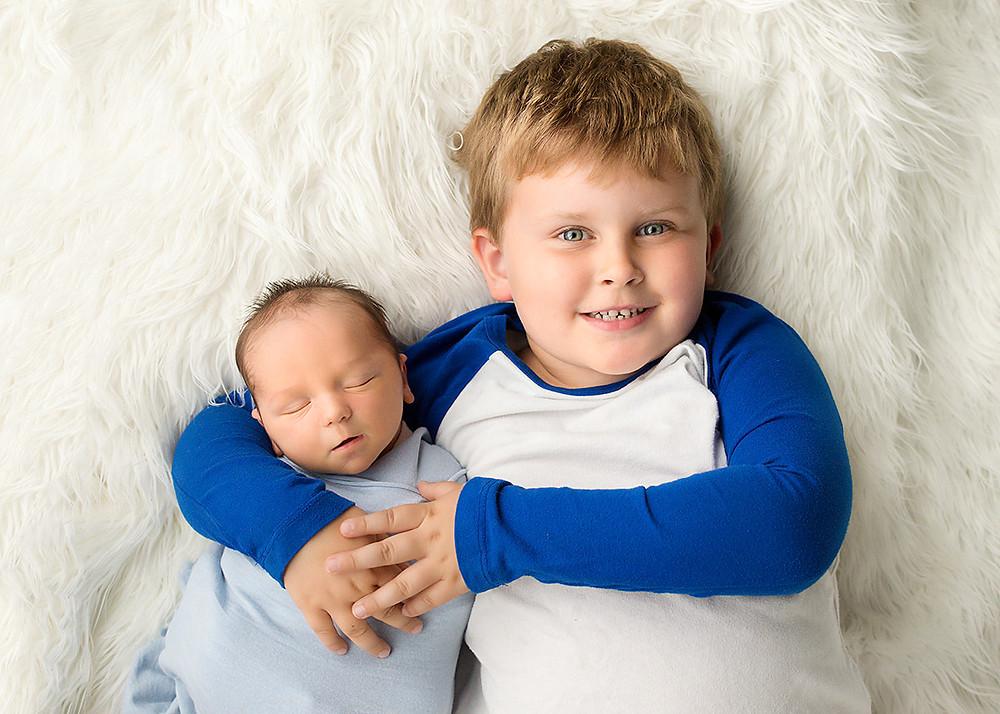 big brother holding newborn baby brother