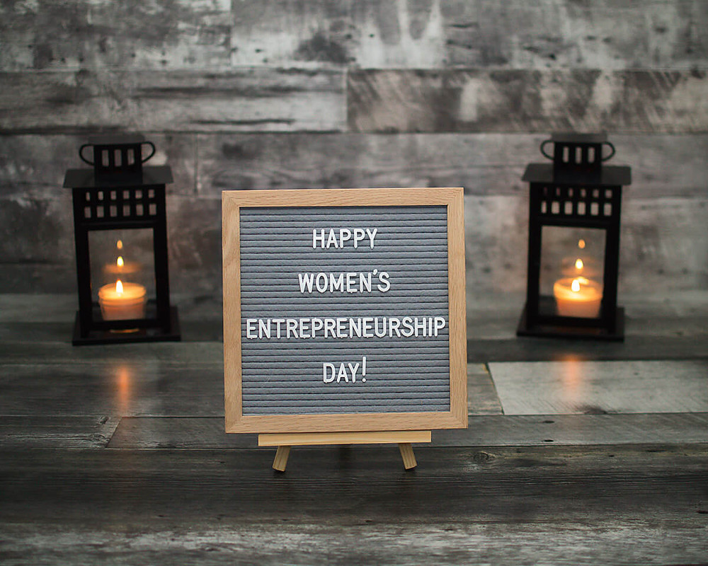women's entrepreneurship day letter board sign with candles in lanterns