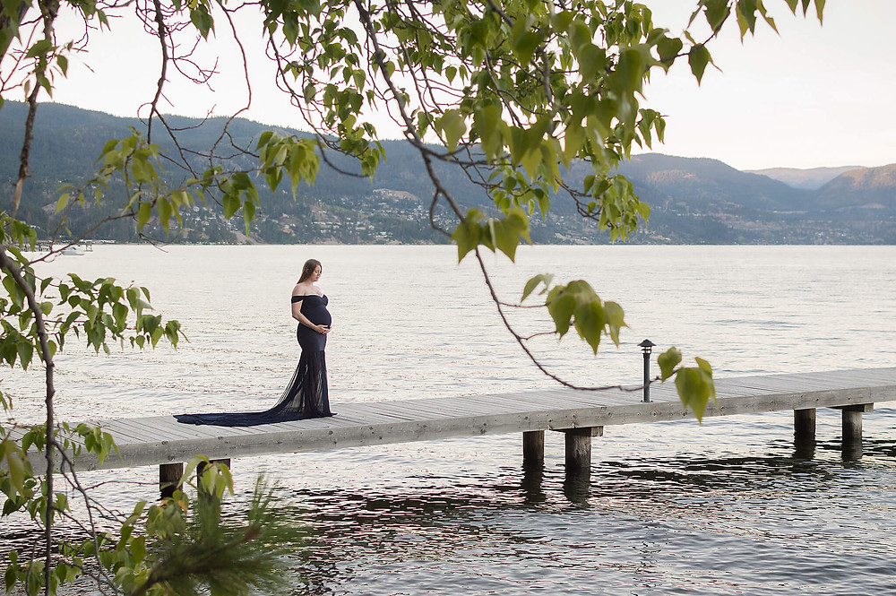 Peachland Maternity Photographer, Nicole Hemeon Photography - pregnant mom holding belly on a dock in peachland for maternity photos