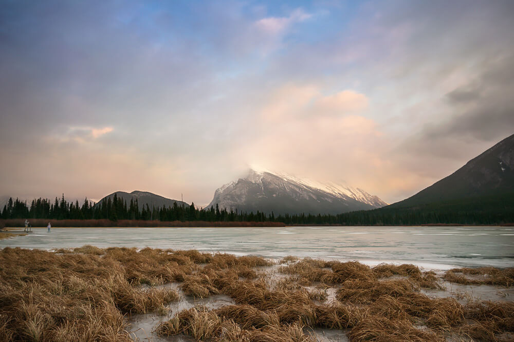 frozen vermillion lakes in banff with mount rundle in the distance