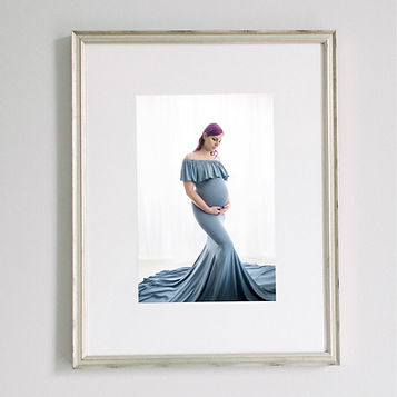 framed matted photo of pregnant mom in blue dress holding belly