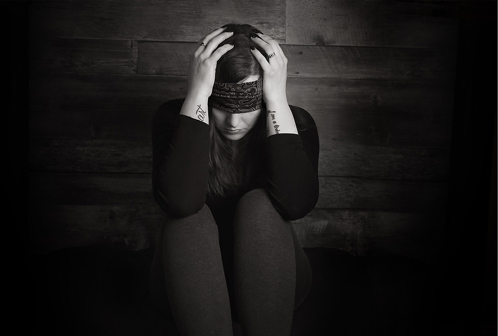female dealing with depression holding her head wearing a blindfold