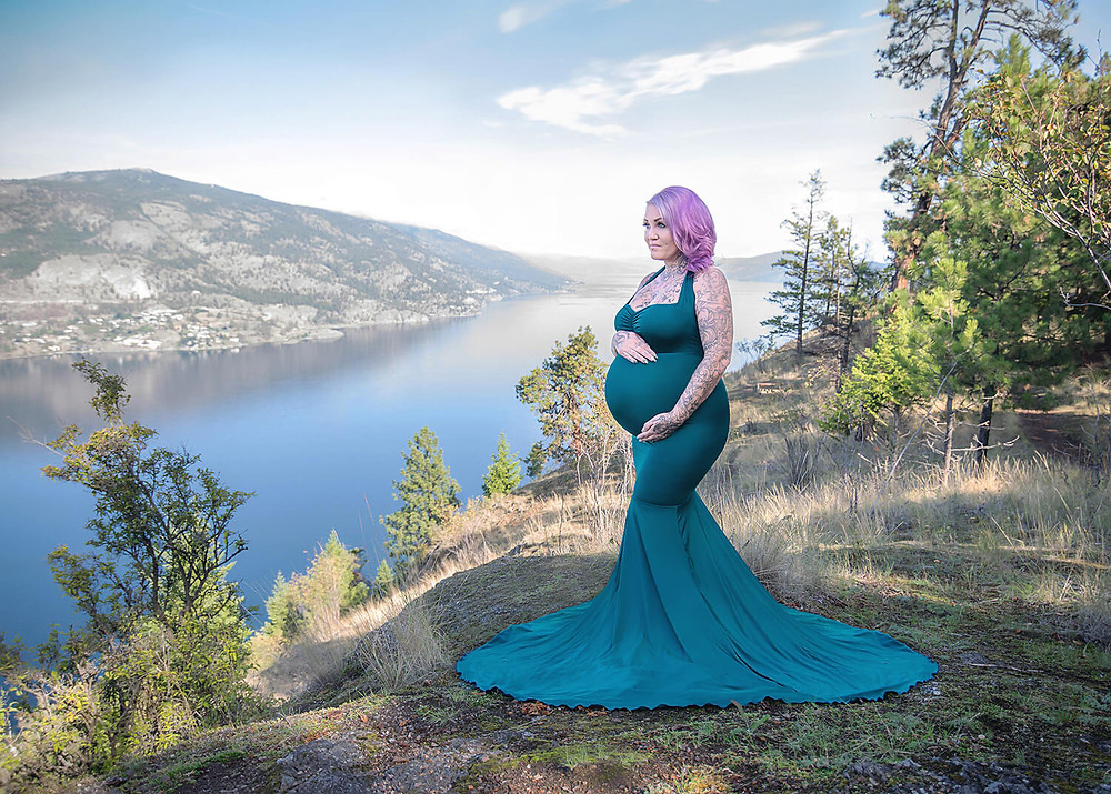 Pregnant mom holding belly, wearing green mermaid maternity dress on Knox Mountain in Kelowna