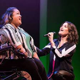 A woman of color in a motorized wheelchair wear a black and whie blazer and green top, singing on stage with international star Idina Menzel. The two women are singing together on stage.
