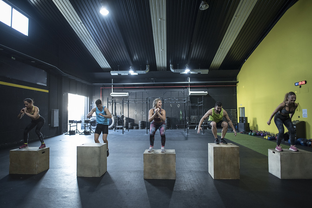 5 men and women in a CrossFit class using plyometric training to jump onto boxes
