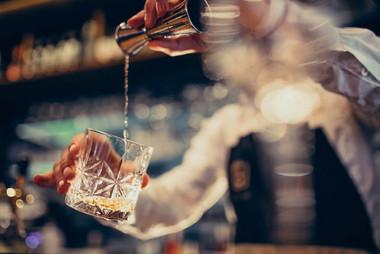 whiskey-handsome-bartender-making-drinking-cocktails-counter.jpg