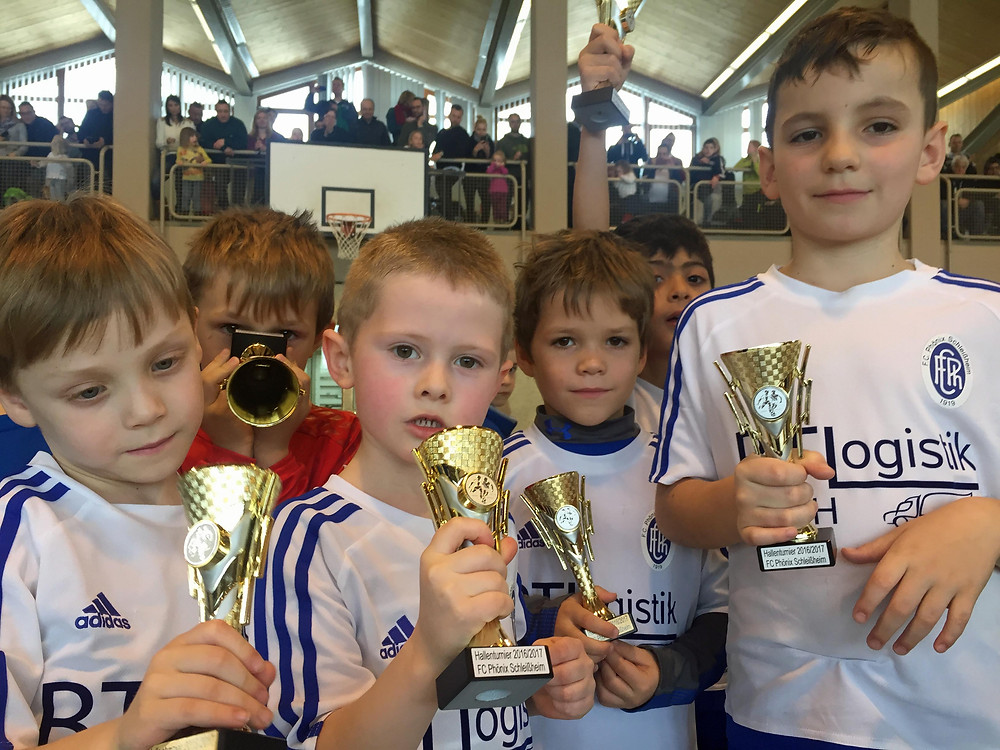 Stolz präsentieren die Jungs ihre Pokale (im Bild unsere G1-Junioren). Im Hintergrund Eltern und Fans, die stolz auf ihre kleinen Fußballer sind.