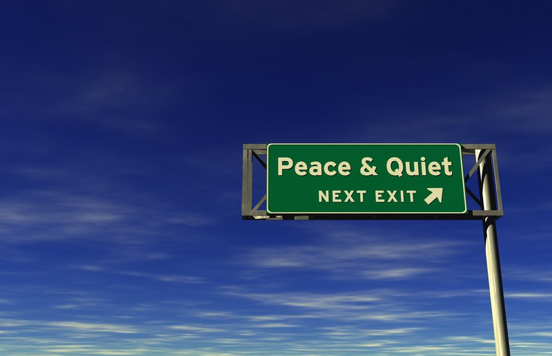 """Green road sign with white writing saying """"Peace & Quiet next exit"""""""
