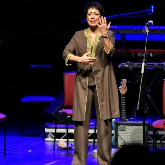 Beverley Roberts standing up and wearing a brown trouser suit. She is signing BSL and standing on stage in front of a guitar and amp