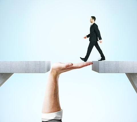 Businessman crossing abstract hand bridge on blue background.jpg