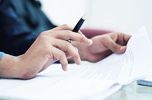 Person looking at documents with pen in hand